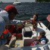 Gloucester: Ken Leonard of Manchester hands his daughter Mia, 5, a hotdog from Dirt's Dogs on the Annisquam River as Mia and her friends, Jack Ancevic, 9, and Griffin Ancevic, 7, right, sit on the 1967 Glasspan cabin cruiser Mia Bella Saturday afternoon.  Staff photo by Mary Muckenhoupt
