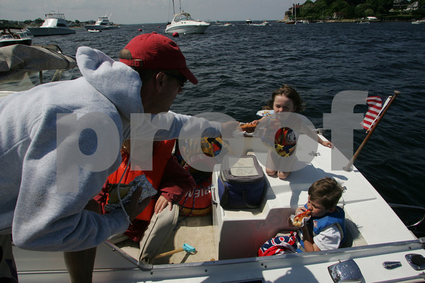 Gloucester: Ken Leonard of Manchester-by-the-Sea hands his daughter Mia, 5, a hotdog from Dirt's Dogs on the Annisquam River as Mia and her friends, Jack Ancevic, 9, and Griffin Ancevic, 7, right, sit on the 1967 Glasspan cabin cruiser Mia Bella Saturday afternoon.  Staff photo by Mary Muckenhoupt