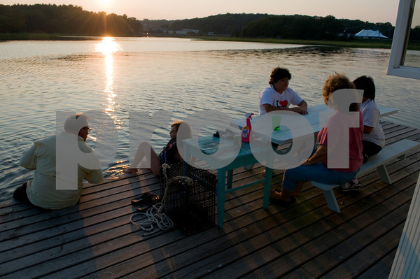 Brett Ramsey, left, sits with his daughter Brie, 10, friend Nicholas Soares, 11, son Nicolas, 8, and wife Ellen on the deck of the houseboat as the sun goes down on Little River. Photo by Desi Smith.