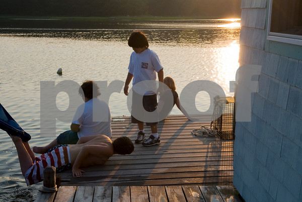 Max Ramsey, 11, left, pulls himself on the deck of the families houseboat  while his friend Nicholas Soares, 11,  his brother Nicholas, 8, and  sister  Brie, 10,  play before dinner.  Photo by Desi Smith