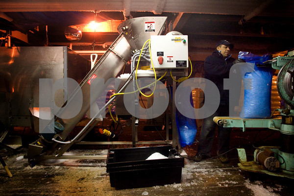 Gloucester: Carlos Hernandez bags ice at Cape Pond Ice where they send out an estimated 500,000 bags of ice every year. Roger Darrigrand Cape Ann Magazine