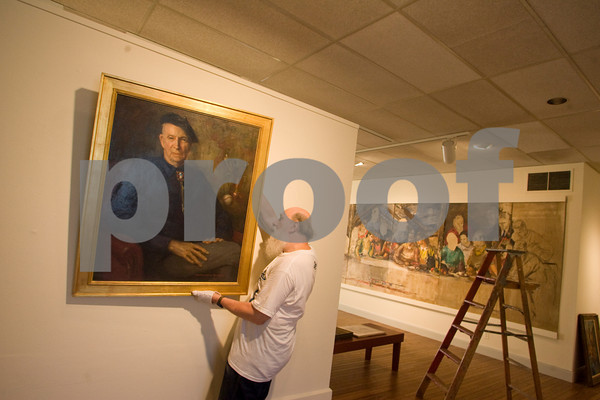 Gloucester: Facilities manager Paul Miller hangs a painting by Rockport artist Marguerite Pearson of Aldro Hibbard for the show Art is Long, Life is short: Rockport Artists in the 1930s at the Cape Ann Museum Thursday morning. Photo by Mary Muckenhoupt