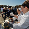 Essex: Amanda Jensen and Lucy Williamson fill cups of Clam Chowder, while Marketing Manager Molly Andrew Williamson of Emerson Inn Rockport (black cap) adds some pepper to a visitors Cup, at the Essex Clamfest held Sunday afternoon. Desi Smith Photo/Gloucester Daily Times. October 25,2009