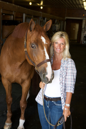 Gloucester native Melissa Lovasco, President and CEO of Fidelity Jumper Classic stands with Tenacious, an eight-year-old stallion at the Silver Oak Equestrian Center in Hampton Falls, New Hampshire <br /> The show jumping event will be held September 15-19, and features five full days of competition that will showcase the talents of some of the world's top riders, successful adult competitors, up and coming junior riders, and some of the top horses in the country.<br /> Amy Sweeney/Staff photo.