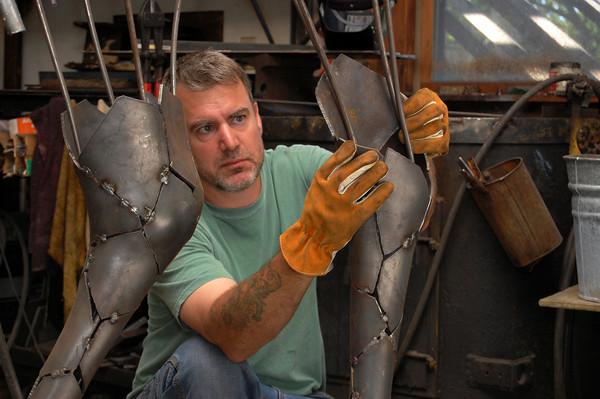 Sculptor Chris Williams fits pieces of the legs on the metal framework of his current life-size moose project for Simon Malls in his studio at 22 Rocky Hill Road, Essex, Mass. Photo by Brianna Healy.