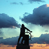 Gloucester: The Man at the Wheel on Stacey Boulevard faces a colorful sky at sunset Wednesday.   Photo by Mike Dean<br /> Wednesday, January 7, 2004