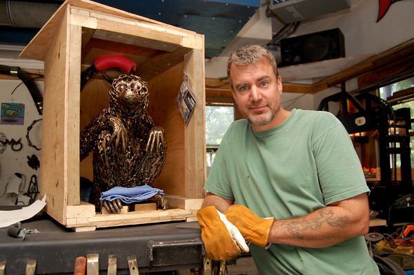 Sculptor Chris Williams stands alongside his first monkey statue in his studio at 22 Rocky Hill Road, Essex, Mass. Photo by Brianna Healy