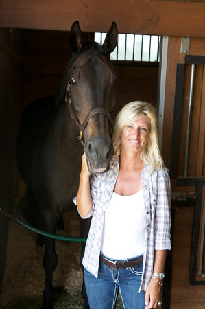 Gloucester native Melissa Lovasco, President and CEO of Fidelity Jumper Classic stands with Glory Days, a German Westphalian, at the Silver Oak Equestrian Center in Hampton Falls, N.H.  She has forged the Jumper Classic into an Olympic-caliber multi-million-dollar endeavor.<br /> Amy Sweeney/Staff photo