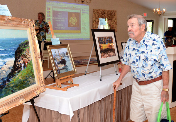 Essex: Gloucester resident Lee Harrington looks over a painting done by John Nesta, before the start of the live Auction held at Woodman's Function Hall. Desi Smith/Gloucester Daily Times. July 21,2011