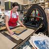 Jim Vaiknoras/Cape Ann Magazine: Julia Garrison sets a  printing block on a tea towel inside of The Sarah Elizabeth Shop in Rockport