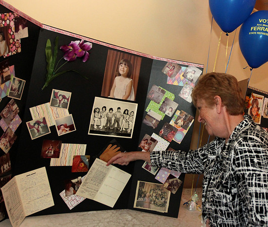 ALLEGRA BOVERMAN/Cape Ann Magazine. At the 40th Birthday Party for State Rep. Ann-Margaret Ferrante at Cruiseport on June 22. Noreen Brennan of Danvers looks at memorabilia compiled for the event, such as Ferrante's sixth grade report card.
