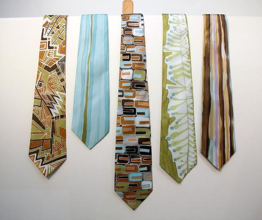 "ALLEGRA BOVERMAN/Cape Ann Magazine. Hand-painted 100 percent silk ties by Adriana ""Gigi"" Mederos of Aquatro Gallery in Rocky Neck. From left: ""Earth Geo,"" $95, ""Aqua Stripe,"" $75, ""Geek Chic,"" $87, ""Chlorophyll,"" $75, ""Brown Stripe,"" $75."