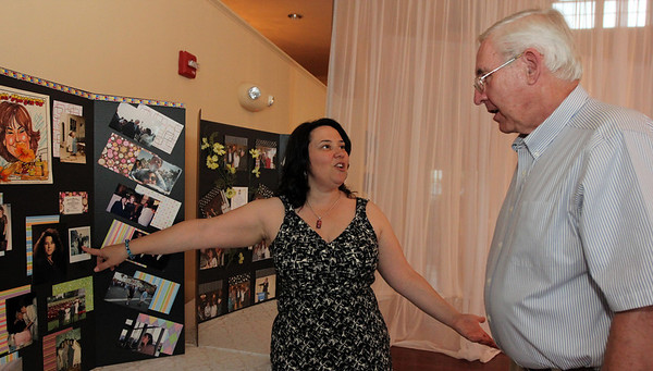 ALLEGRA BOVERMAN/Cape Ann Magazine. At the 40th Birthday Party for State Rep. Ann-Margaret Ferrante at Cruiseport on June 22. Ferrante, left, shows John Brennan of Danvers a photo of herself with Ronald Reagan.