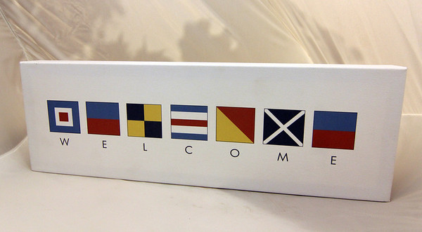"ALLEGRA BOVERMAN/Cape Ann Magazine Advertise your open door policy and add a Cape Ann flavor to the office with this handpainted canvas, which spells ""welcome"" with nautical flags. It comes in two sizes: the smaller size is $34, the larger, $54. Harbor Loop Gift Shop at the Building Center, 1 Harbor Loop, Gloucester, 978-283-3060,  <a href=""http://www.bcgloucester.com/giftshop"">http://www.bcgloucester.com/giftshop</a>."