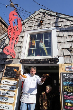 ALLEGRA BOVERMAN/Cape Ann Magazine Kenny Porter of Rockport, left, and Rune DeFort, 7, of Rockport, at Roy Moore's Lobster Shack in Bearskin Neck.