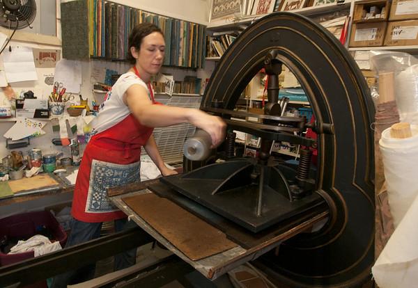 Jim Vaiknoras/Cape Ann Magazine: Julia Garrison uses her block printer on a tea towel inside of The Sarah Elizabeth Shop in Rockport