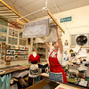 Jim Vaiknoras/Cape Ann Magazine: Julia Garrison hangs a tea towel from a rack hanging from the ceiling inside of The Sarah Elizabeth Shop in Rockport.