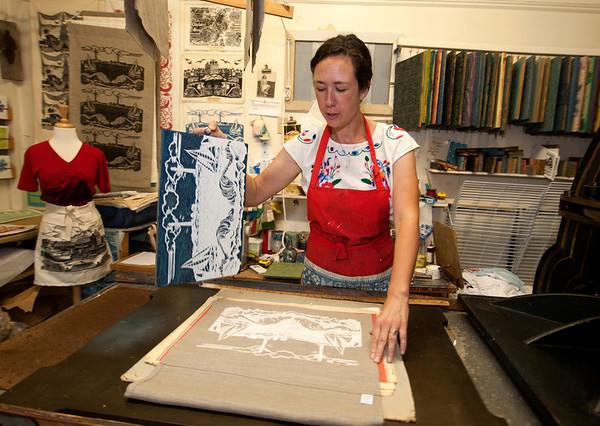 Jim Vaiknoras/Cape Ann Magazine: Julia Garrison peels back a  printing block on a tea towel inside of The Sarah Elizabeth Shop in Rockport