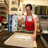 Jim Vaiknoras/Cape Ann Magazine: Julia Garrison peels back a  printing block on a tea towel inside of The Sarah Elizabeth Shop in Rockport