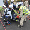 Desi Smith/Gloucester Daily Times.  North Andover Fire Fighter John Weir (in basket) is safe on the ground after being lowered some 400 feet from insde the Varian wind turbine on Dory Road, Gloucester by Ipswich Fire Lt. Andy Theriault (left) in a rescue training exercise with the The Essex County Technical Rescue Team Wednesday afternoon. October 18, 2013.