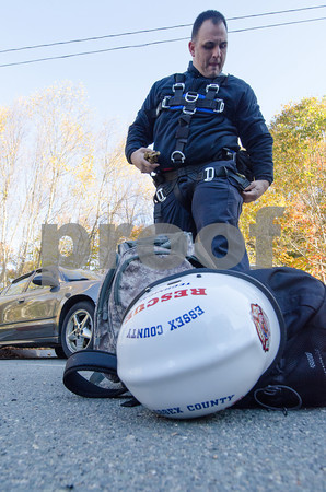 Desi Smith/Cape Ann <br /> Lawrence firefighter Paul King attaches his Class 3 safety harness as he and the rest of the Essex County Technical Rescue Team take part in a rescue drill at Varian Semiconductor's 400-foot wind turbine off Dory Road   in Gloucester on Oct. 25, 2013.
