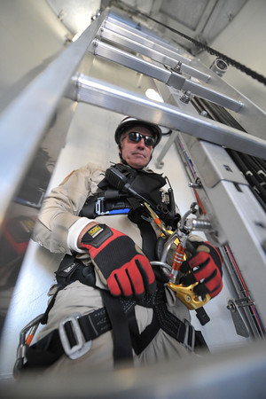 "Desi Smith/Cape Ann<br /> Peabody firefighter Dan Dean attaches himself to the ""lift assist,"" a motorized pulley which will help up the ladder inside Varian Semiconductor's 497-foot tall wind turbine on Dory Road in Gloucester. Dean, a member of the Essex County Technical Rescue Team, was working with team on mock rescue drill on Oct. 25, 2013."