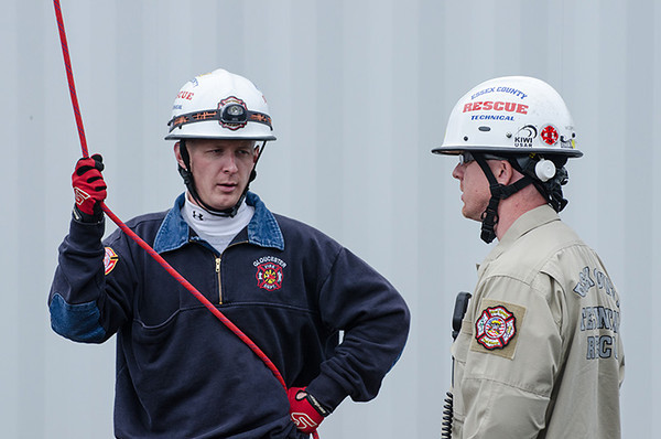 Desi Smith/Cape Ann<br /> Gloucester firefighter Nicholas Ouellette, a member  of the Essex County Technical Rescue Team, talks to another member about a mock rescue drill held at 497-foot Varian Semiconductor wind turbine on Dory Road in Gloucester.