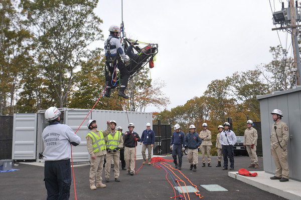 Members of the The Essex County Technical Rescue Team watch as Ipswich Fire Lt. Andy Theriault, in air, lowers down North Andover firefighter John Weir, in basket, to the ground as Gloucester firefighter NicholasOuellette, far left, holds a tether line in a rescue training exercise with the The Essex County Technical Rescue Team Wednesday at the Varian Semiconductor wind turbine on Dory Road, Gloucester October 18, 2013.