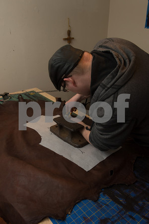 Desi Smith/Cape Ann<br /> Paul Durgin of Bearskin Neck Leathers uses a heavy antique boat cleat to help keep both the deerhide and pattern flat while he cuts a piece for coat.