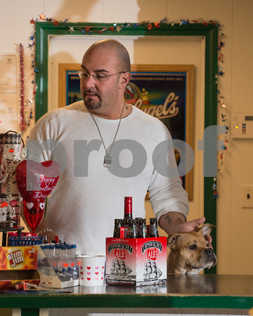 Desi Smith/Cape Ann<br /> Vinnie Marano of Essex Wine & Spirits on Main Street, Essex, works the counter as Mumma, a 3-year-old American Pit Bull Terrier, checks out a customer shopping for more spririts.