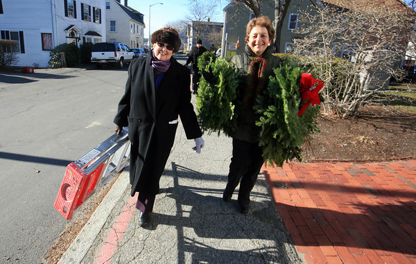Jan Bell, left, and Gail Sarafeen carry decorations up to City Hall after decorating Middle Street in December 2010. Amy Sweeney/Staff photo.