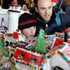Gloucester: Nathan Spencer checks out the fist place winner of the gingerbread contest with his sons Calvin, 8, and Jason, 6 months, on Spencer's back, at City Hall in December 2008.  Mary Muckenhoupt/Gloucester Daily Times