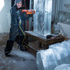 Desi Smith/Cape Ann<br /> Sean Patrick uses an electric chainsaw to cut a tropical fish from a large block of ice in the Cape Pond Ice icehouse.