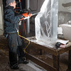 Desi Smith/Cape Ann<br /> Sean Fitzpatrick, in the Cape Pond Ice icehouse, uses an electric chainsaw to trim large chunks from an ice block that will become a tropical fish.