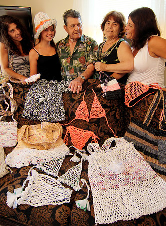 """ALLEGRA BOVERMAN/Staff photo. Gloucester Daily Times. Gloucester: Accursio """"Gus"""" and Francesca Alba of Gloucester, center, make tote bags, hats, purses and other wearable items out of woven plastic bags. They are flanked, from left, their daughter Dianne Jackson, granddaughter Macaella Oliver, 13, and, at far right, daughter Sandra Sanfilippo."""
