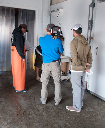 """A Compass Seafood employee signs paperwork required by the government when a bluefin tuna is landed and sold while Capt. Dave Carraro, left, and a """"Wicked Tuna"""" camera crew watch. Desi Smith photo"""