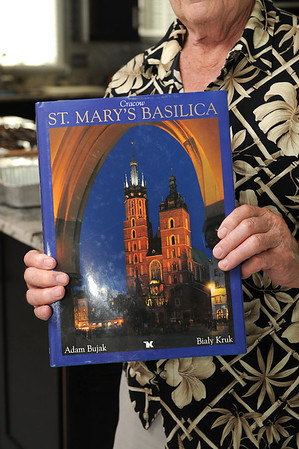 Curtis Dagley holds up a book about St. Mary's Basilica in Krakow, Poland. Dagley was arrested in World War II while guarding a train carrying a 15th century altarpiece now housed in the church. Dagley had committed no crime but was used as a pawn by the U.S. and Polish Communist governments. Photo by Desi Smith.