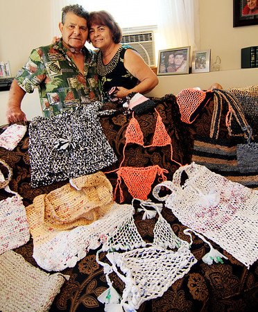 """ALLEGRA BOVERMAN/Staff photo<br /> Accursio """"Gus"""" and Francesca Alba of Gloucester with an assortment of tote bags, purses and other wearable items they have woven from plastic bags."""