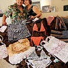 "ALLEGRA BOVERMAN/Staff photo<br /> Accursio ""Gus"" and Francesca Alba of Gloucester with an assortment of tote bags, purses and other wearable items they have woven from plastic bags."