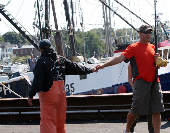 """Bounty Hunter Capt. Bill Monte, left, and a """"Wicked Tuna"""" fan greet each other.<br /> Photo by Allegra Boverman."""