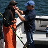 "During the filming of promotional stills and video at Gloucester Marine Railways in Rocky Neck for the second season of ""Wicked Tuna"" in mid-September, an Evolve IMG sound technician, right, wires Capt. Dave Carraro of the FV-Tuna.com. Photo by Allegra Boverman."