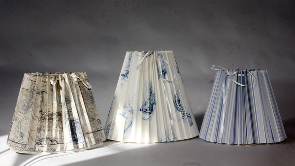 """Clever Covers. These pleated lampshade slipcovers are handmade by Ariana Barron of Rockport, and of La Provence, 4 Main Street, Rockport. They adjust to fit over an existing lampshade of any shape. Two sizes, 12 inches, $26, (center) and 9 inches, $22, (right and left) with adjustable width.  Also available at  <a href=""""http://www.shopclevercovers.comPhoto"""">http://www.shopclevercovers.comPhoto</a> by Allegra Boverman."""