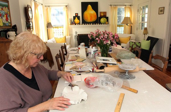 Anna Kasabian of Manchester. Her studio is actually spread across several rooms in her house including her dining room and its table, and kitchen. She has various stations set up on the table for the various stages of her porcelain work production. Photo by Allegra Boverman.