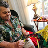 """ALLEGRA BOVERMAN/Staff photo<br /> Accursio """"Gus"""" and Francesca Alba of Gloucester make tote bags, purses and other wearable items out of woven plastic bags. Gus's hands fly as he weaves the bags into a new design, this one in Boston Bruins colors."""