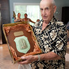 Curtis Dagley holds up a plaque the he received honoring him as a hero from the parishioners of St. Mary's Basilica in Krakow, Poland. Dagley played a part in saving the church's 15th century hand-carved altarpiece during World War II. Photo by Desi Smith.