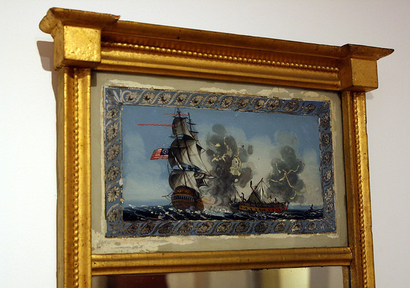 """Photo Courtesy of the Cape Ann Museum. This looking glass, or mirror, dates from 1815-1820 and is on display in the Cape Ann Museum galleries. The reverse painting on glass depicts the battle between the Constitution and Guerriere off the coast of Cape Ann, one of the most heralded skirmishes of  the War of 1812. After one cannon-ball bounced """"harmlessly"""" off the side of the Constitution, a crew member is said to have yelled """"Huzzah! Her sides are made of iron!"""" This battle, the first of several U.S. Navy victories in ship-to-ship contests, encouraged Americans and chagrined the British."""