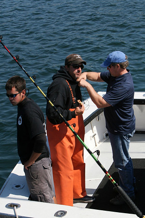 "During the filming of promotional stills and video at Gloucester Marine Railways in Rocky Neck for the second season of ""Wicked Tuna"" in mid-September, an Evolve IMG sound technician wires deckhand Sandro Maniaci, left, and Capt. Dave Carraro, center, of the FV-Tuna.com. Photo by Allegra Boverman."