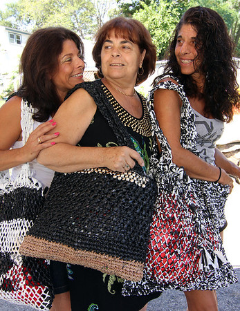 """ALLEGRA BOVERMAN/Staff photo. Gloucester Daily Times. Gloucester: Accursio """"Gus"""" and Francesca Alba of Gloucester make tote bags,  purses and other accessories. Francesca, center, wears one of their tote bags adorned with metallic pieces. With other totes the couple made are their daughters Sandra Sanfilippo, left, and Dianne Jackson."""