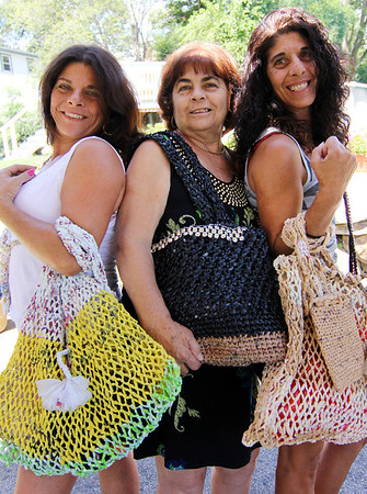 """ALLEGRA BOVERMAN photo<br />  Accursio """"Gus"""" and Francesca Alba of Gloucester make tote bags, purses and other accessories. Francesca, center, wears one of their tote bags adorned with metallic pieces. With other totes the couple made are their daughters Sandra Sanfilippo, left, and Dianne Jackson."""