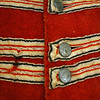 Rob Bibelhauser/Cape Ann Museum. Detail of a British red coat from the War of 1812. The coat is made of wool, with cotton details and brass buttons
